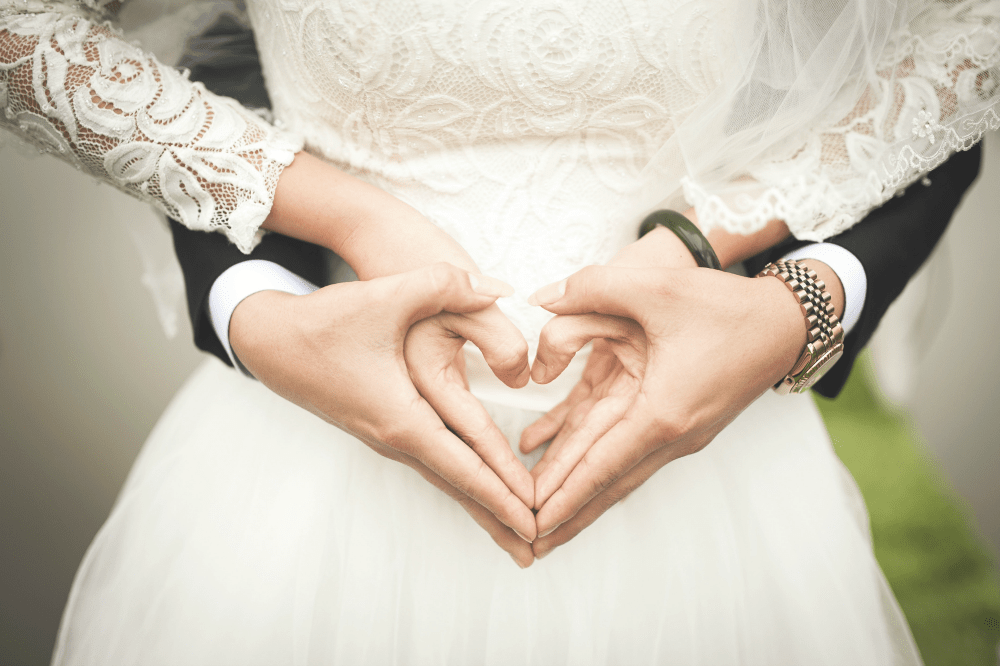 young married couple with heart hands