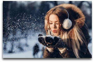 girl blowing snow flakes in winter