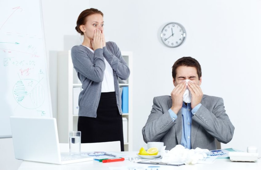 co-workers sneezing and spreading germs