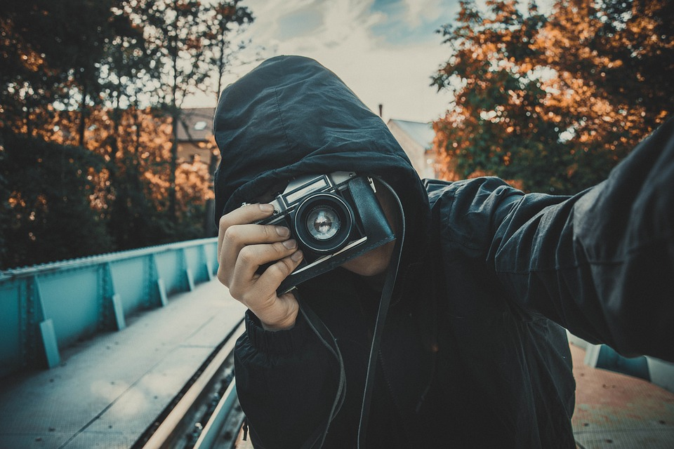 young guy in hoodie taking a picture